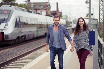 lächelndes paar geht den bahnsteig entlang