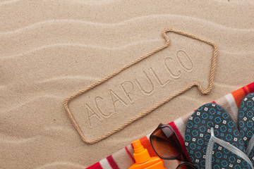 Acapulco pointer and beach accessories lying on the sand