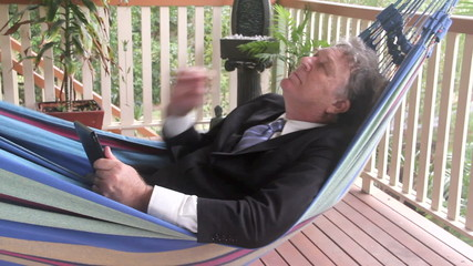 Businessman swinging in hammock working on tablet.