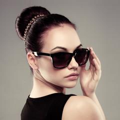 Close-up of beautiful brunette model in stylish sunglasses