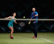 Woman player and her coach practicing on a tennis court