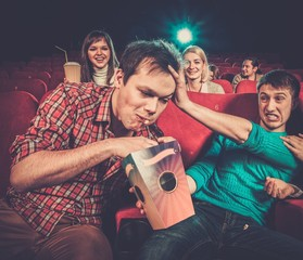 Impudent young man steals popcorn in cinema
