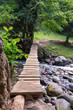 Suspended wooden bridge across mountain river