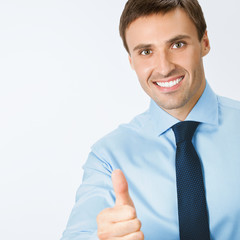 Businessman with thumbs up gesture, on grey