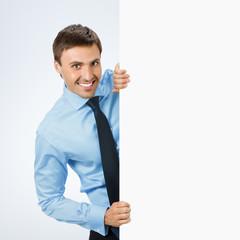 Businessman showing signboard, on grey