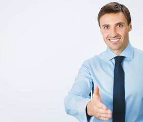 Business man giving hand for handshake, on grey