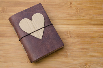 old notebook on a wooden table with a cardboard heart on top