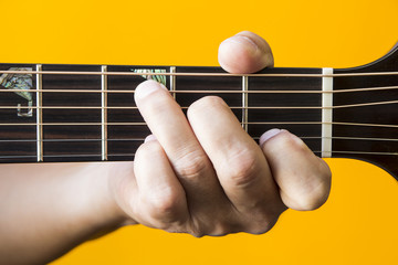 Hand performing C major chord on guitar
