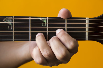 Hand performing D chord on guitar