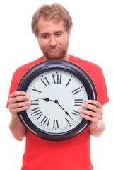 Sad bearded man holding big clock on white