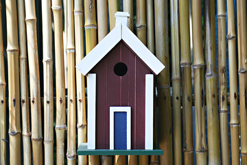 Brown and white wood nesting box for birds on the bamboo wall