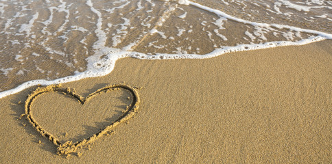 Heart drawn on ocean beach sand.