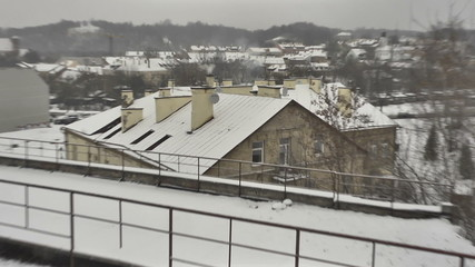 Vilnius. Winter. Snow-covered roof. Сhimneys smoke. Zoom in