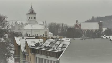 Vilnius. Winter. Snow-covered roof. Сhimneys smoke. Pan.