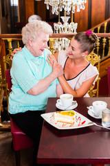 Oma und Enkelin lachen bei Kaffee und Kuchen