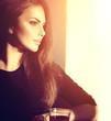 Beautiful brunette girl drinking tea or coffee in cafe