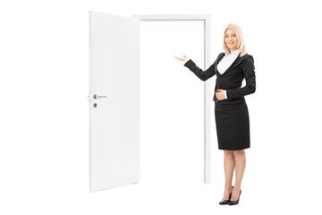 Female real estate agent pointing towards a door