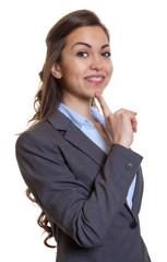Frau im grauen Blazer schaut verträumt