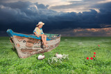Old boat with a little girl on the meadow