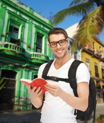 happy young man with backpack and book travelling