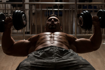 Bodybuilder Exercising Chest With Dumbbells