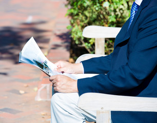 Businessman reading a newspaper outdoors outside
