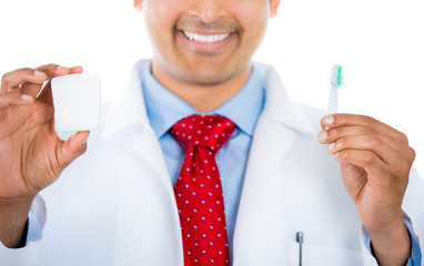 Closeuop dentist holding a toothbrush and dental floss