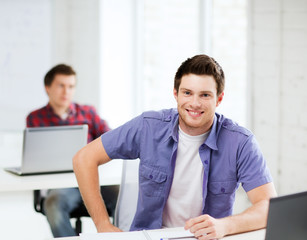 smiling student with laptop at school