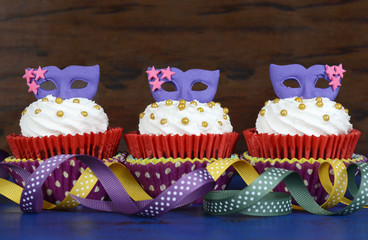 Mardi Gras cupcakes with purple mask toppers
