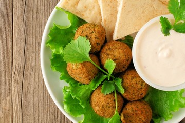 Plate of falafel with pita bread and tzatziki sauce close up