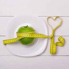 Apple and centimeter on the plate. Fitness healthy eating