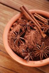 ciotola di terracotta con cacao, cannella e anice stellato
