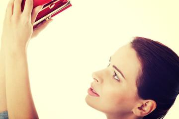 Beautiful woman showing her empty wallet.