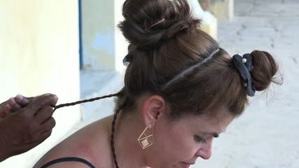 Tourist woman getting little braids hairdo in Old Havana