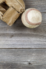 Used baseball and weathered mitt on old wood