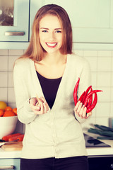 Woman is holding chili peppers and garlic.