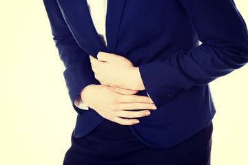 Business woman is touching her stomach.