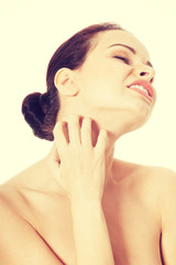 Young beautiful woman is scratching her neck.