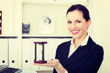Business woman holding hourglass.