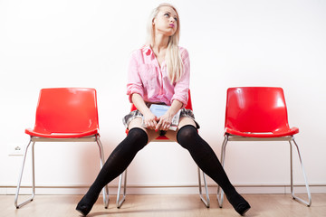 blonde student girl in a waiting room bored