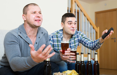 Two male sport fans watching game at home