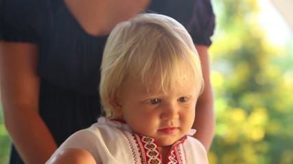 small blonde baby girl iwatching cartoon and crawl away