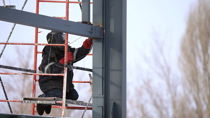 Welder operating at the height, weld metal beam together