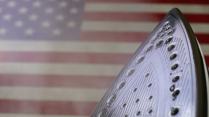 Iron releasing steam on a flag of the USA in 4K UHD video.