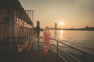 Young woman admiring the sunset over river in city