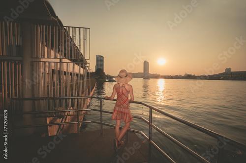 Młoda kobieta podziwia zmierzch nad rzeką w mieście