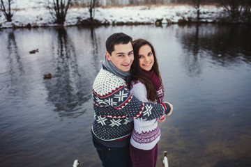 Positive couple smiling, standing in a winter park near the lake
