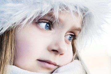 Pretty blue-eyed girl who warms his hands frozen in a cold day