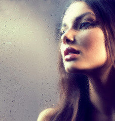 Portrait of beauty girl behind the wet glass. Melancholy. Rain