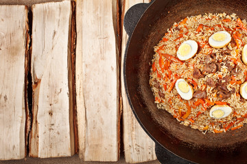 traditional central asia pilaf in kazan on logs